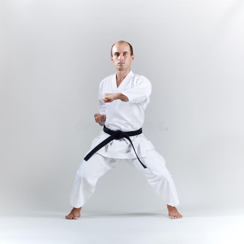 Auf einem hellen Hintergrund bildet ein erwachsener Sportler eine formale Karateübung in einem weißen karategi aus lizenzfreie stockbilder