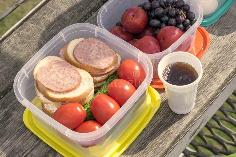 Auf einem Holztisch in einem Plastikbehälter ist Gemüse: Tomaten und Gurken sowie Sandwiche mit Wurst stockfotos