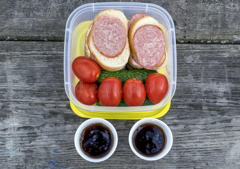 Auf einem Holztisch in einem Plastikbehälter ist Gemüse: Tomaten und Gurken sowie Sandwiche mit Wurst stockfotografie