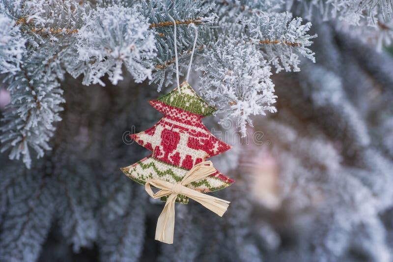 Auf einem schneebedeckter Baumast hängenden Weihnachtsspielzeug handgemacht stockfoto