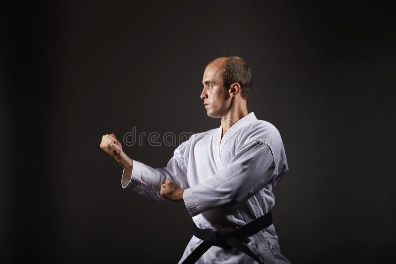 Auf einem schwarzen Hintergrund bildet ein Athlet eine formale Karateübung aus lizenzfreie stockfotos
