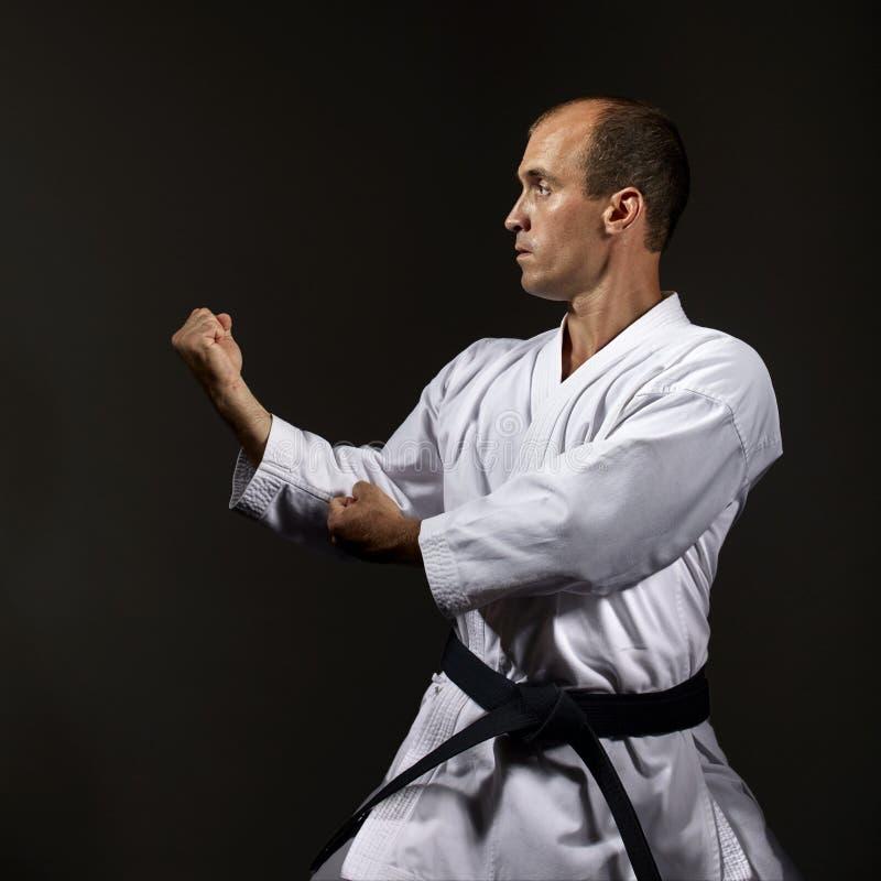 Auf einem schwarzen Hintergrund führt der Athlet die formalen Übungen von Karate durch lizenzfreie stockfotos