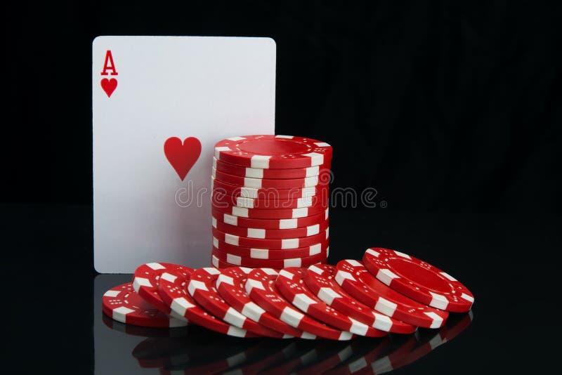 Auf einem schwarzen Hintergrund mit Reflexion, Nahaufnahme der höchsten Karte und roten Chips für das Spielen des Schürhakens, mi lizenzfreies stockfoto