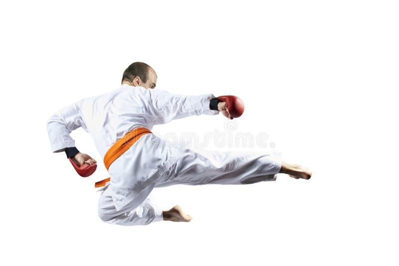 Auf einem weißen Hintergrund schlägt ein Athlet einen Tritt in einem Sprung stockfotos
