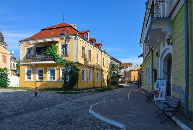 Auf einer alten Straße mit zweistöckigen Häusern ist ein einsames kleines Mädchen stockbilder