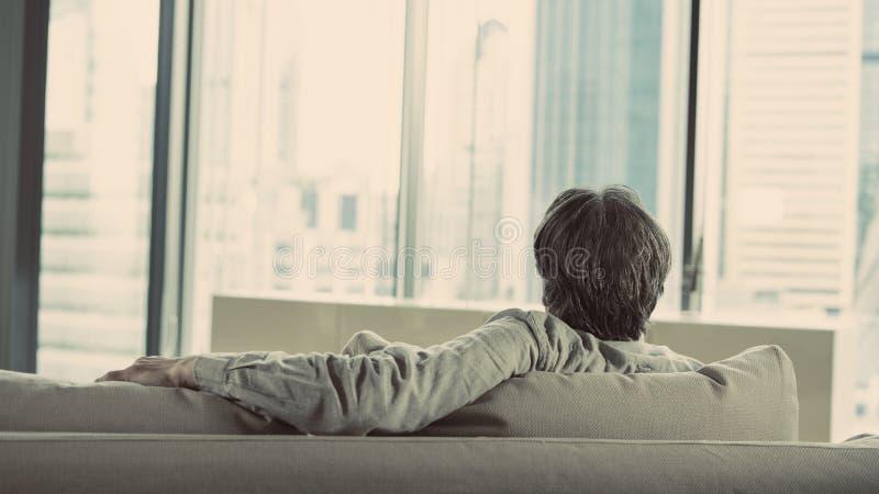 Auf einer Couch zu Hause sich entspannen stockfotografie