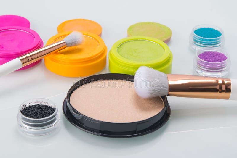 Auf einer hellen Tabelle, Einzelteilen für Make-up, bunten Schatten, Pulver und Bürsten für das Zutreffen lizenzfreie stockfotos