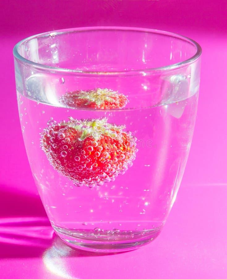 Auf einer rosa Hintergrunderdbeere in einem Glas Blasen stockfotografie