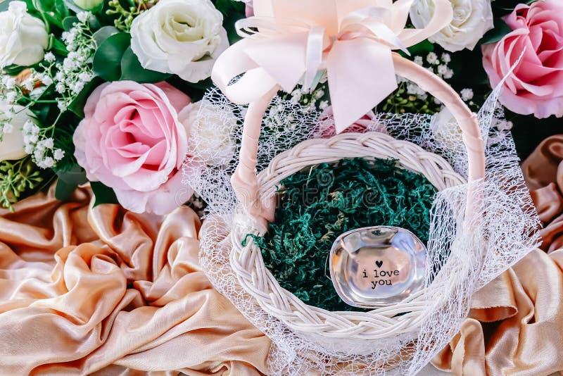 Auf einer Tabelle ist ein Korb mit den rosafarbenen Blumenblumenblättern für die Heiratszeremonie stockfotos