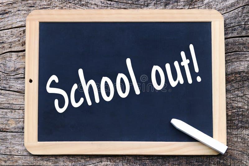 Auf einer Tafel wird mit Kreide geschrieben: Schule heraus lizenzfreie stockbilder
