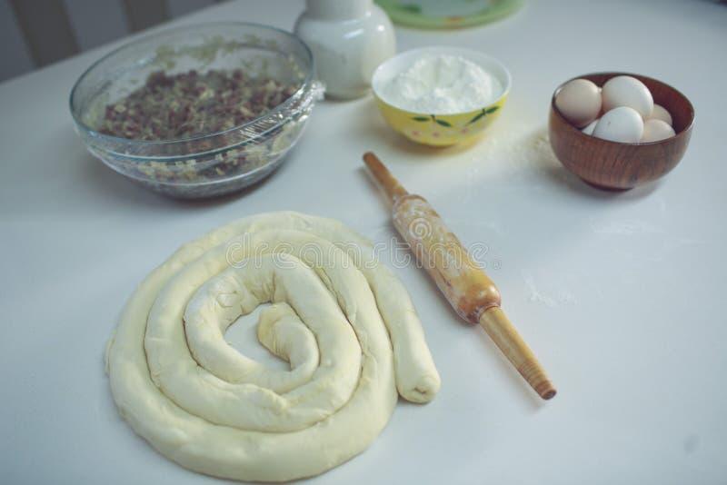 Auf einer weißen Tabelle eine Schüssel mit den Eiern und Mehl, bereit, oben gerollt zu werden und nahe bei dem Nudelholz Ansicht  lizenzfreie stockfotografie