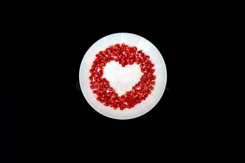 Auf einer weißen Platte von der zusammengesetzten Herzform der Granatapfelsamen Schwarzer Hintergrund Flache Schicht lizenzfreies stockfoto