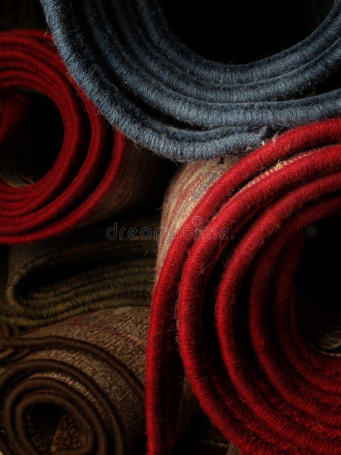 Auf Lagere gerollte Teppiche stockbild