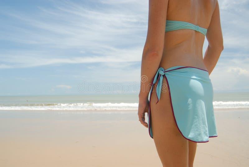 Auf lagerfoto der schönen hohen Brunettefrau auf dem Strand in stockfotografie