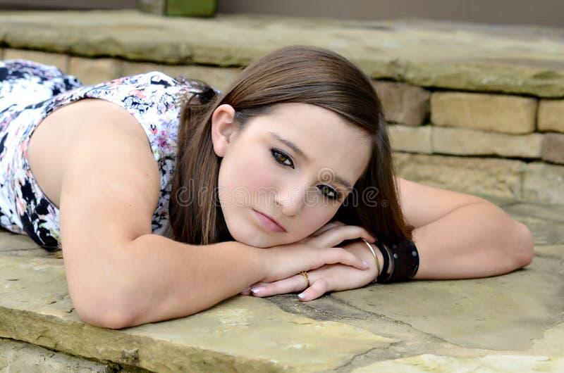 Auf lagerfoto eines Mädchens gegen blaue Wand lizenzfreies stockbild
