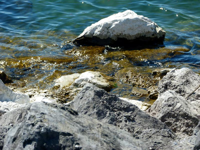 Auf lakeshore mit Steinen und einer leichten Welle stockfotografie