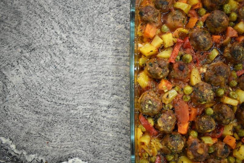 Auf Marmorboden Fleischklöschen mit Gemüse, in der Glasbackform lizenzfreie stockfotografie