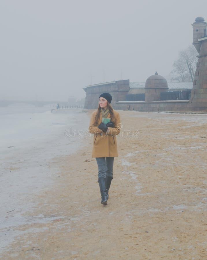 Auf Steinwandhintergrund ist schönes Mädchen auf dem sandigen Strand im Winter, in den Händen des Buches lizenzfreie stockfotografie