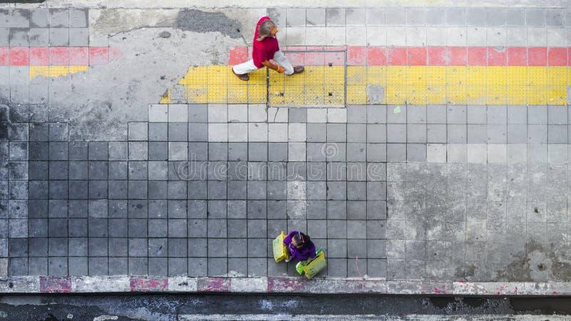 Auf Straßenweg im Draufsichtmann und -frau mit Einkaufstaschen lizenzfreie stockfotografie
