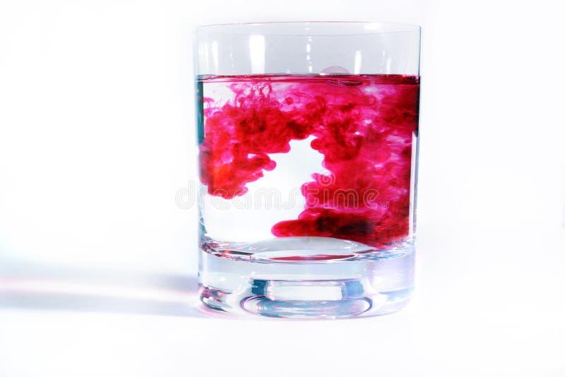 Auf transparenten Gläsern eines weißen Hintergrundes mit Wasser, in jeder Tropfenfängerrotfarbe Tintenunschärfen im Wasser, bilde stockfoto