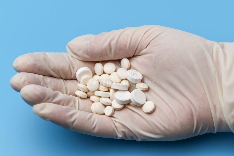 Auf weißem medizinischem Latex ist ein Handschuh eine Handvoll der weißen Pillennahaufnahme Medizinischer Hintergrund Das Fragmen lizenzfreie stockfotos
