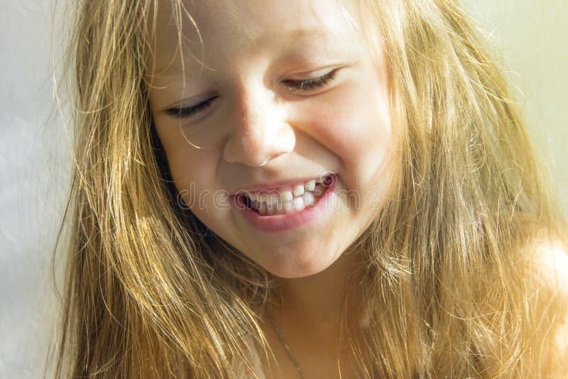 Auf weißer Hintergrund dem schönen dunkelhaarigen Brunettemädchen mit dem ungepflegten langen Haar lächelnd, gelbe Beleuchtung ab lizenzfreies stockfoto