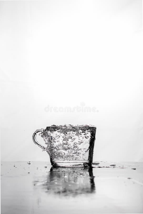 Auf weißem Hintergrund ein Becher, in dem Wasser sprudelt Kopieren Sie Platz stockbild