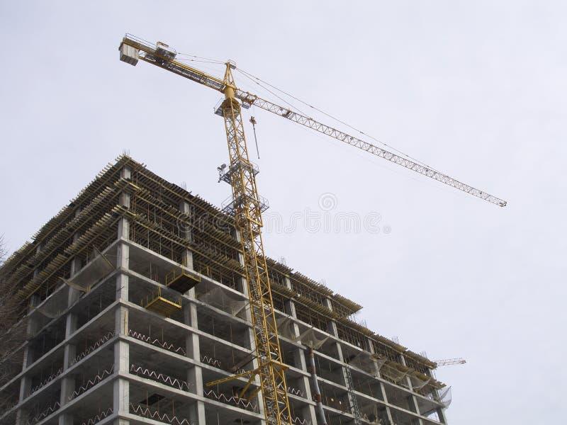 Aufbau, der Kran über Gebäudehaus hochzieht stockfoto
