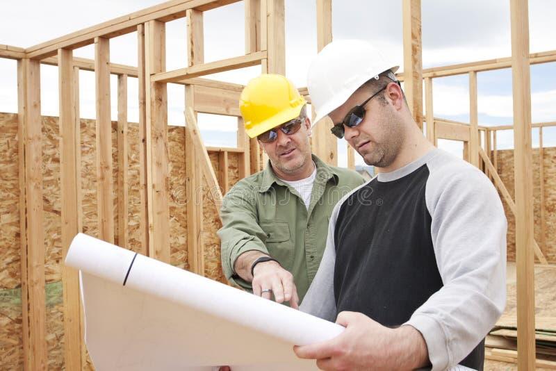 Aufbau-Fremdfirmen, die ein neues Haus aufbauen stockbilder