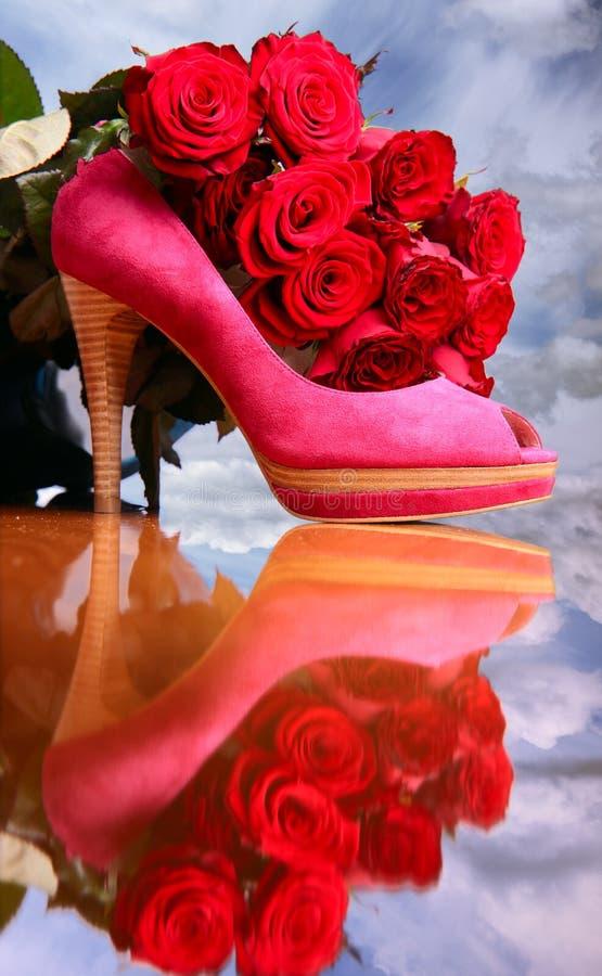 Aufbau mit roten Rosen und rosafarbenem weiblichem Schuh lizenzfreie stockbilder