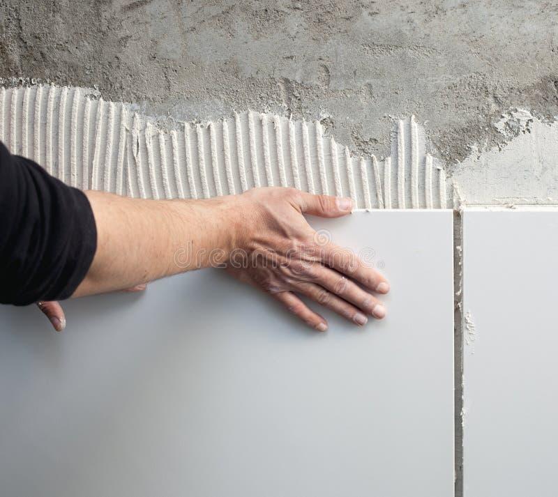 Aufbaumaurer-Mannhände auf Fliesearbeit lizenzfreie stockfotos