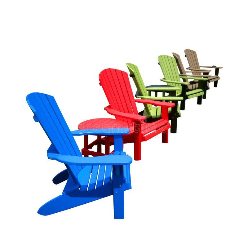 Aufbereitete Plastik- Farbe-Adirondack-Stühle in der Reihe lizenzfreies stockfoto