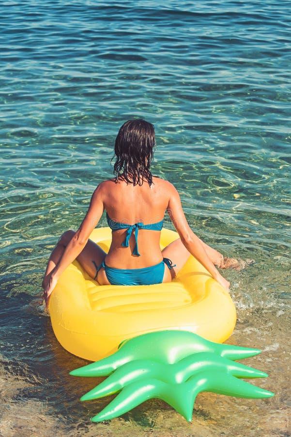 Aufblasbare Matratze, Tätigkeit und Freude der Ananas Sommerferien und -reise zum Ozean Mädchen, das auf Strand mit Luft ein Sonn lizenzfreies stockbild