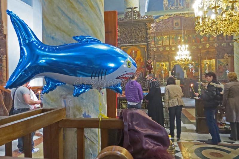 Aufblasbarer Haifisch in der orthodoxen Kirche Steigen Sie für Kinder mit Helium unter betenden Leuten im Ballon auf stockbilder