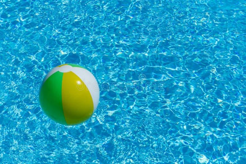 Aufblasbarer mehrfarbiger Ball, der auf Swimmingpoolwasser schwimmt lizenzfreie stockbilder