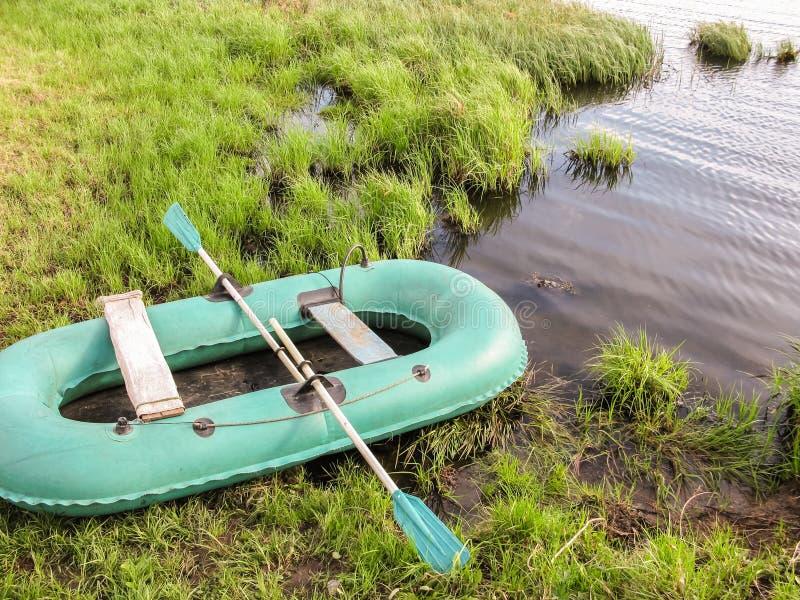 Aufblasbares Boot auf dem grünen Gras durch den See stockfotografie