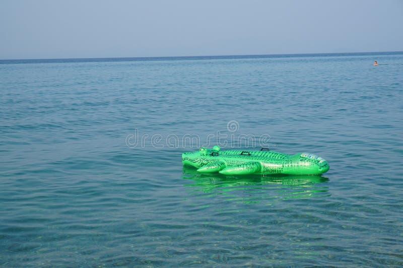 Aufblasbares Matratzenkrokodil auf Wasseroberfläche stockfoto