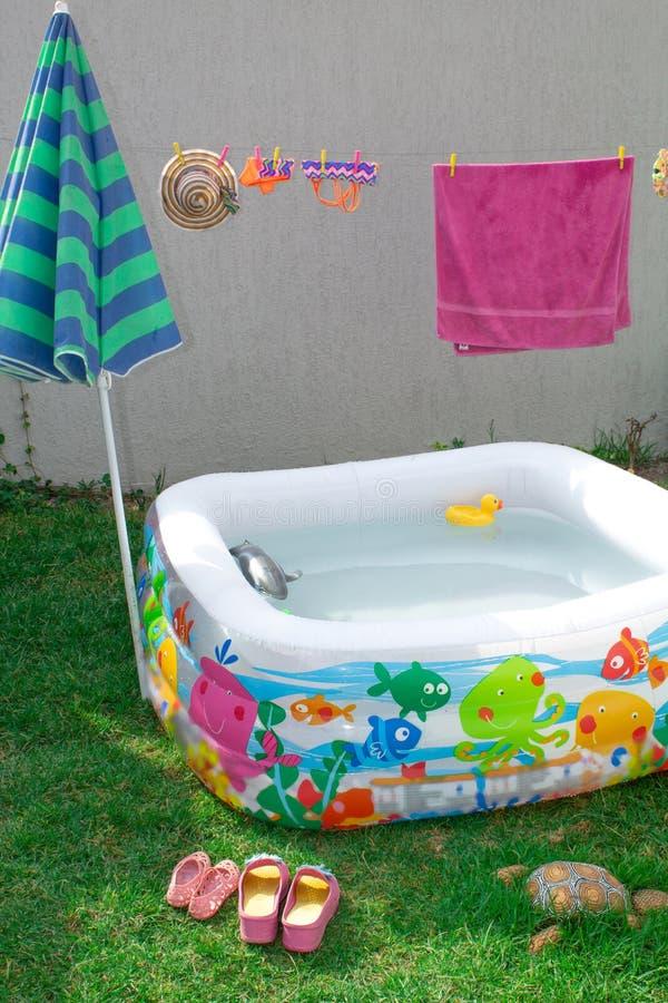 Aufblasbares Pool im Garten, mit einem Regenschirm stockfotografie