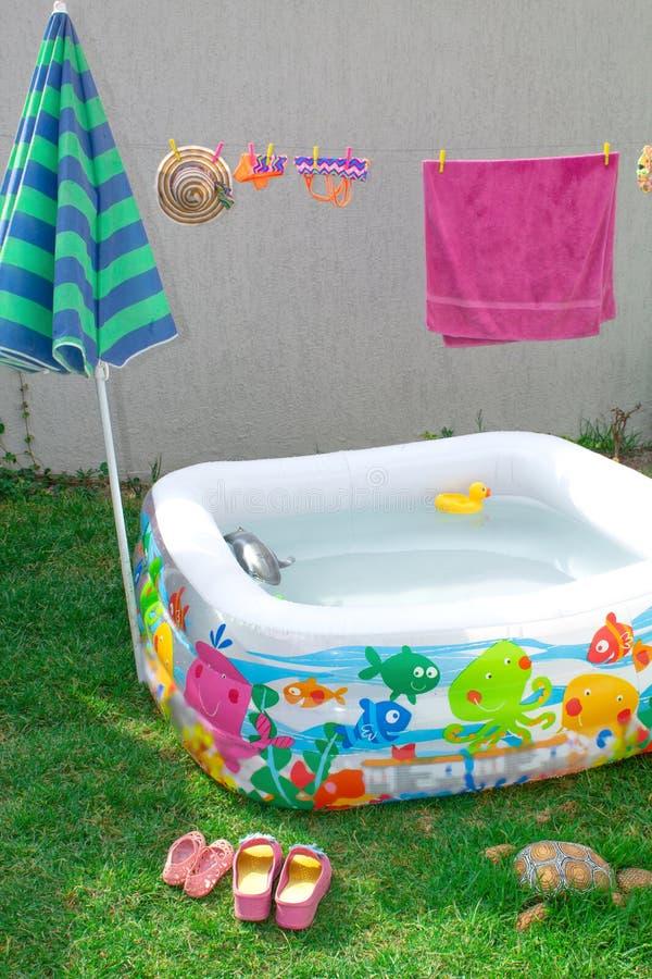 Aufblasbares Pool im Garten, mit einem Regenschirm lizenzfreie stockfotos