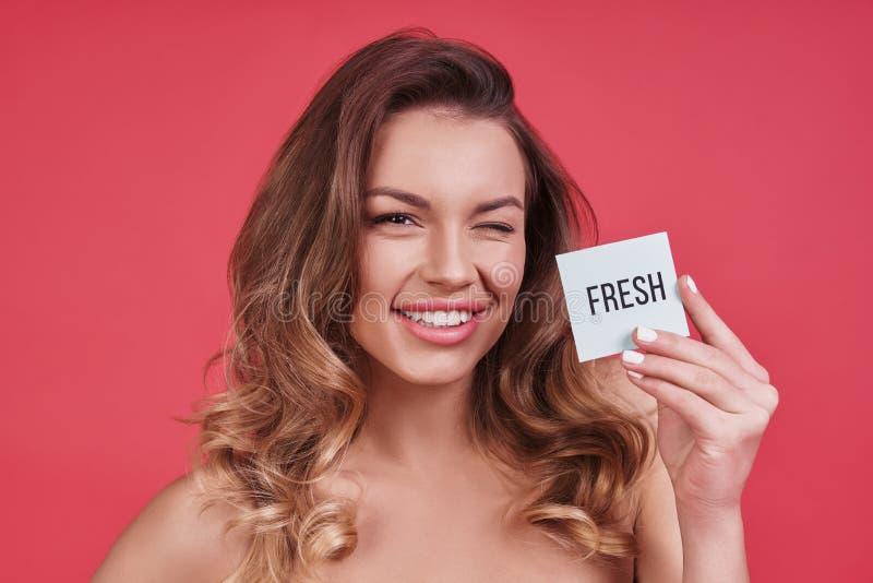 Aufenthalt frisch! Attraktive junge Frau, die ein Plakat blinzelt und hält stockfoto