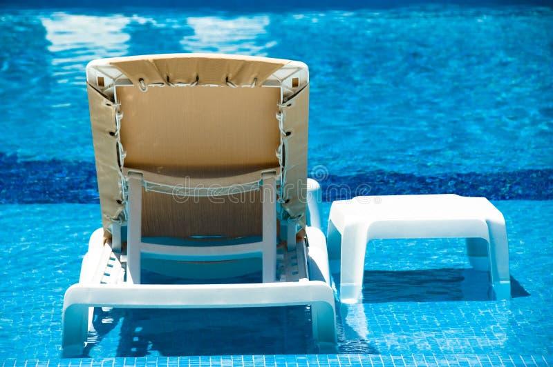 Aufenthaltsraum-Stuhl im Pool lizenzfreies stockfoto