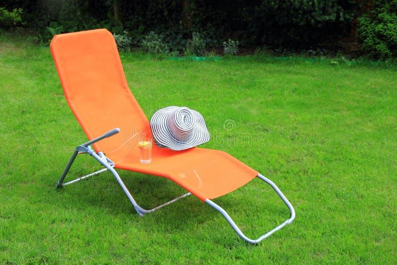 Aufenthaltsraum sunbed Stellung auf grünem Gras stockfoto