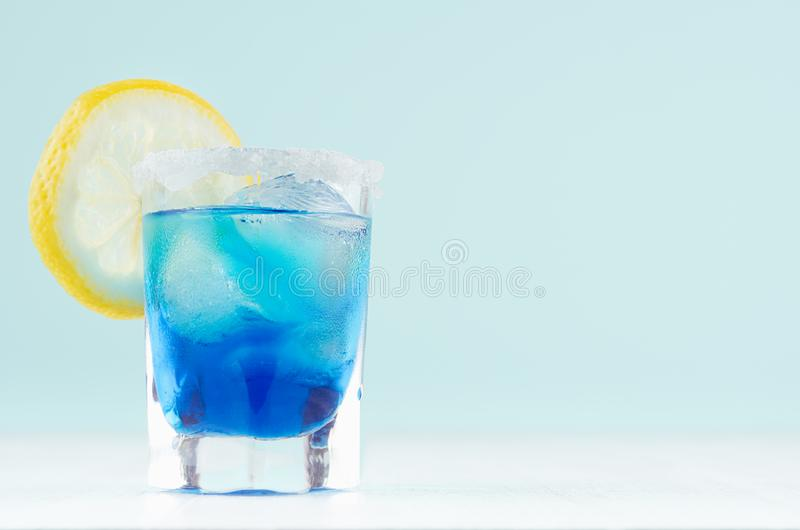 Auffrischungsalkoholgetränk blaues Hawaii in misted elegantem Schnapsglas mit Eiswürfeln, Zitrusfruchtscheibe, Salzkante in der m lizenzfreie stockfotografie