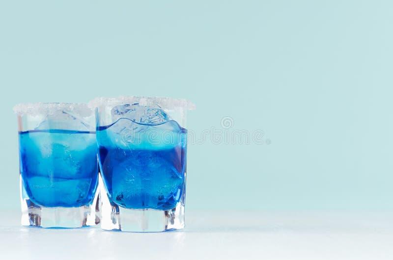 Auffrischungsalkoholgetränke blaues Hawaii in zwei misted elegantes Schnapsglas mit Eiswürfeln und Salzkante in der modernen tade lizenzfreie stockfotografie