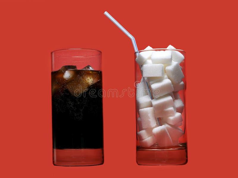Auffrischungsgetränk des Kolabaums und Glas voll von den Zuckerwürfeln und -stroh, die enormen Kaloriengehalt darstellen stockfoto