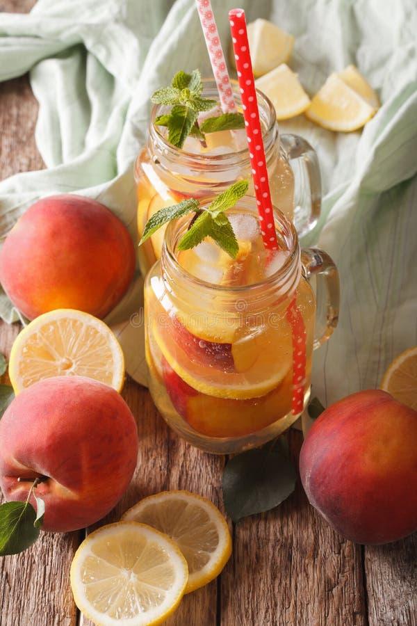 Auffrischungsgetränk mit Zitrone, Pfirsich, Eis und Minze in einem Glasgefäß lizenzfreie stockfotografie