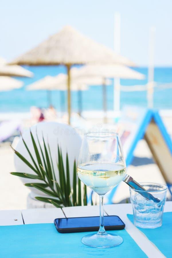 Auffrischungsglas kalter Wein auf einer Tabelle in einem stilvollen Café auf dem Strand stockfotografie