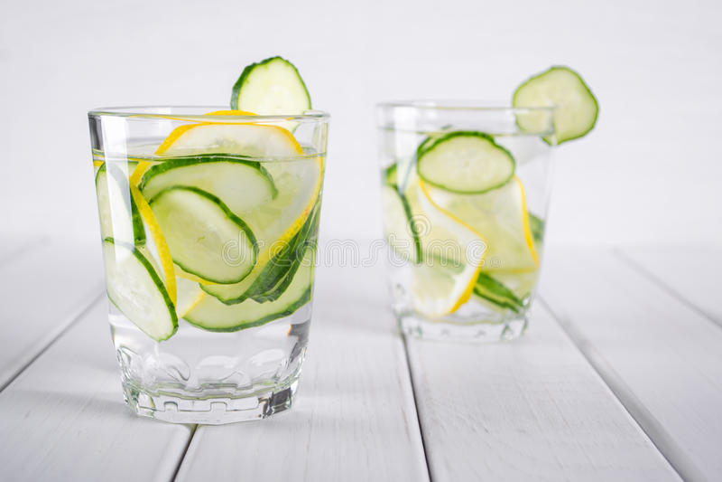 Auffrischungsgurkencocktail, Limonade, Detoxwasser in Gläsern Orange und Carafe mit Zitrusfruchteiswasser lizenzfreie stockfotografie