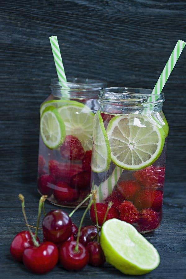 Auffrischungssommergetränk mit Frucht Getränk gemacht von der Kirsche, Himbeere, Kalk Dunkler h?lzerner Hintergrund stockfoto