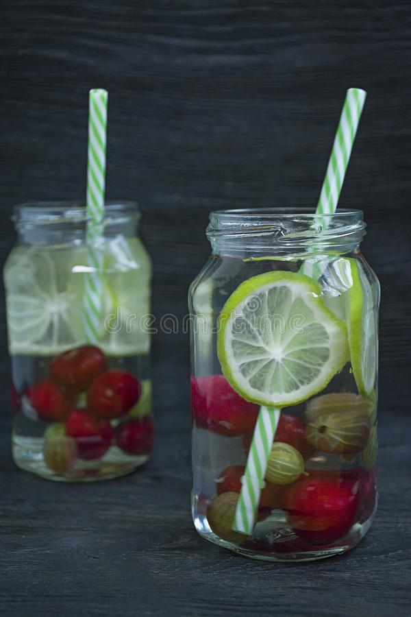 Auffrischungssommergetränk mit Frucht Getränk gemacht von der Kirsche, Stachelbeere, Kalk Dunkler h?lzerner Hintergrund lizenzfreies stockbild